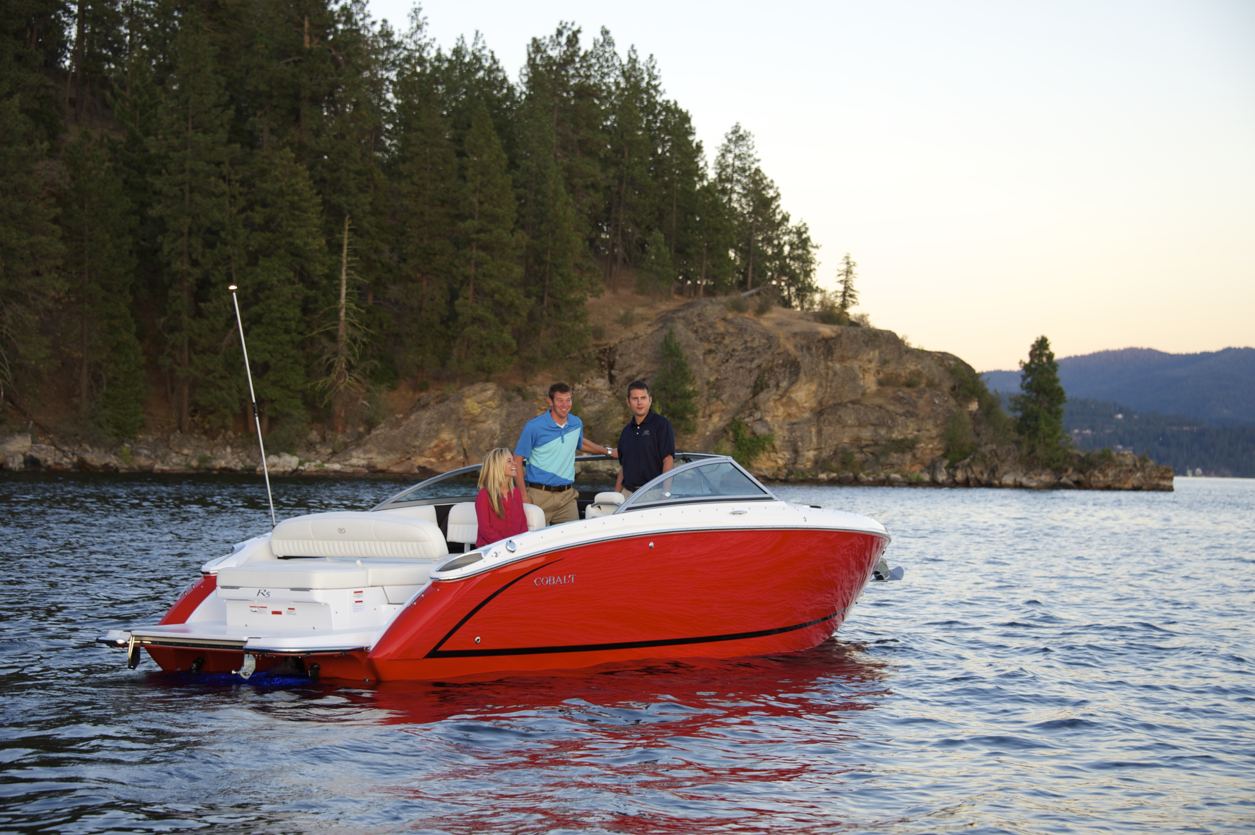 friends smiling and coasting on lake in cobalt runabout boat