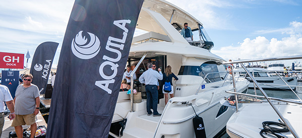 People aboard a docked Aquila power catamaran at a boat show with a black Aquila banner in front