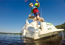 Boy jumping off boat into water