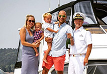 Couple with two young children stand next to a boat captain in front of a boat