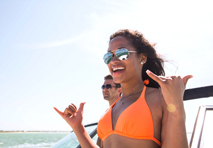 Woman with sunglasses forming shaka hand gestures while speeding down ocean in a yacht