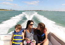 Mom sitting with children in rear of boat speeding away from the coastline