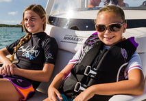 two girls on bow cushion of boston whaler