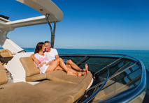 couple in each others arms lounging on deck chairs of yacht