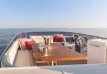 drinks sitting atop high quality wooden table surrounded by leather seating on pontoon