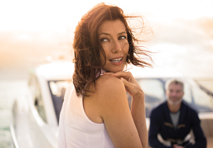 woman in front of yacht peers quizzically over her shoulder