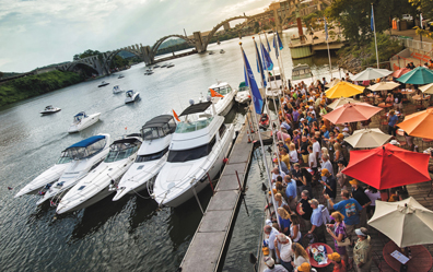 Crowd watches yachts travel down river