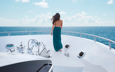 Woman on yacht in turquois dress enjoys warm ocean breeze