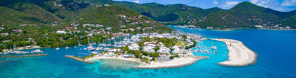 MarineMax Vacations base in tortola. Buildings on an island surrounded by white sandy beach and bright blue waters.