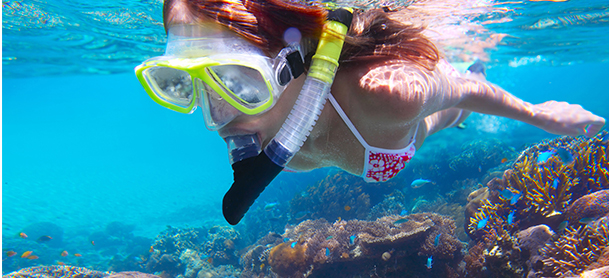women snorkeling with yellow goggles in blue water above a colorful reef
