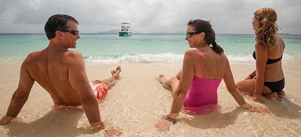 three people in bathing suits relaxing in the sand on a beach with a boat in the background