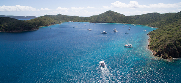 large body of blue water surrounded by green islands with many boats running and anchored