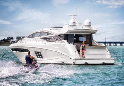 Woman on yacht watches man approach on jetski