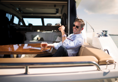Man seated on yacht enjoys a cigar