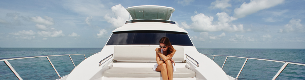 Woman lounges on the front of beautiful yacht