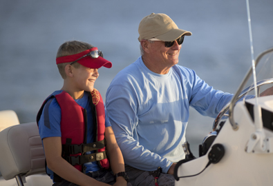Grandfather fishing with grandson on a boat