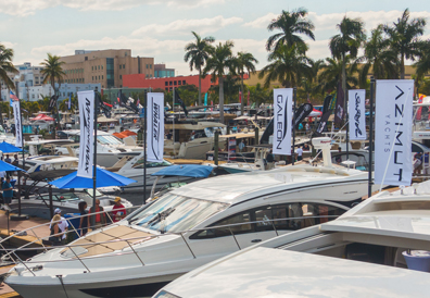 Group viewing yachts of various brands like Azimut and Galeon at boat show