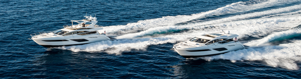 two white sport yachts kicking up waves side-by-side
