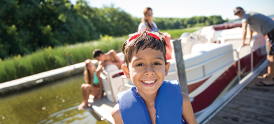 Child smiling in front of pontoon