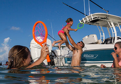 Family in water with Boston Whaler 230 Outrage