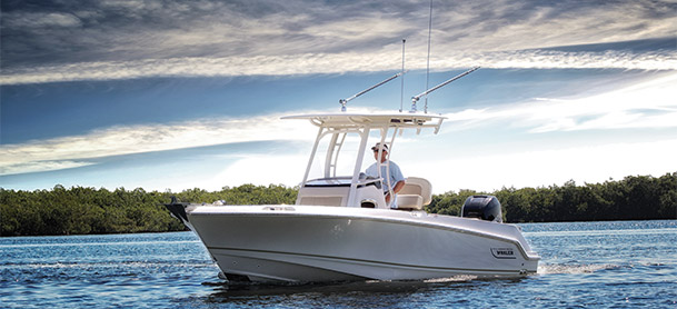 Man driving Boston Whaler 230 Outrage in calm water
