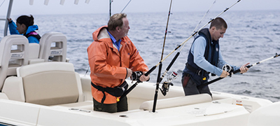 two men in long sleeves preparing their fishing poles on the back of a boston whaler with a woman in the background sitting at the helm