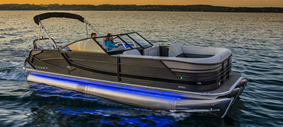 sunset or evening with a crest pontoon still in calm dark waters with glowing blue or purple accent lights on the boat