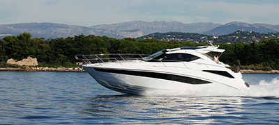White galeon traveling fast on a lake or intracoastal with green hills or mountains in the background