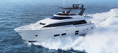 Hatteras 70 Motor Yacht cruising through beautiful blue waters.