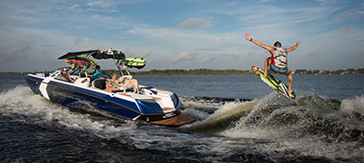 Nautique running  on large lake or open water with  a male wakesurfing on large wake with people watching from the back of the boat