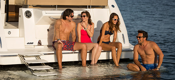 Sea Ray Fly 400 with two couples sitting on swim platform