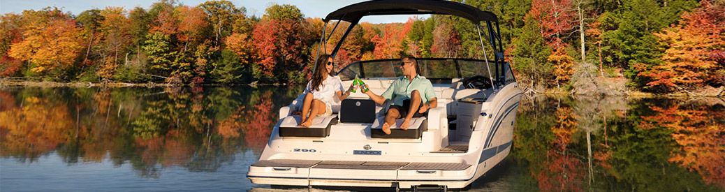Couple on back of Sea Ray SDX 290 enjoying fall weather