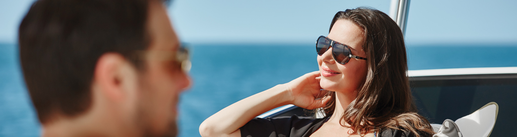 smiling woman on yacht running fingers through hair while taking in the beautiful ocean scenery