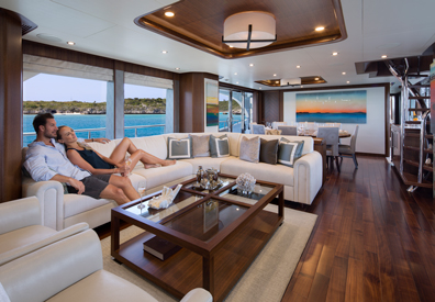 couple lounging on spacious white leather sofa taking in the luxuorious interior furnishing of yacht