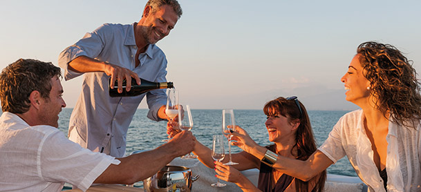 group enjoying champagne on the deck of a yacht