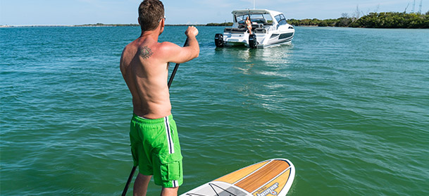man on stand up paddle board in front of boat