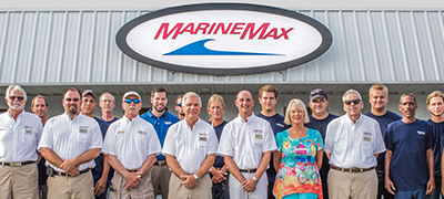Team of MarineMax Employees standing in front of a store with a large sign over head