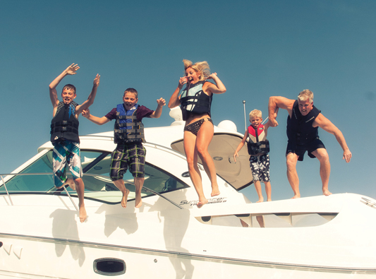 family jumping from yacht into ocean