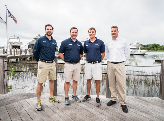 Marinemax employees stand on dock in front of boats