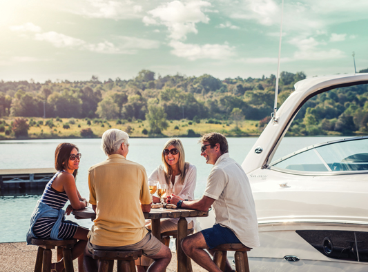 Group sits around table on dock in front of white yacht