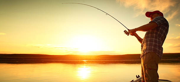 A man fishing in shallow water with a sunset behind him