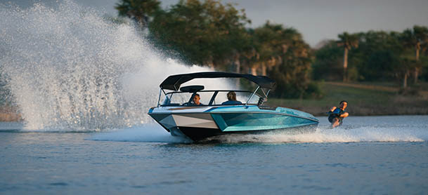 A blue Nautique boat with a wakeboarder behind it