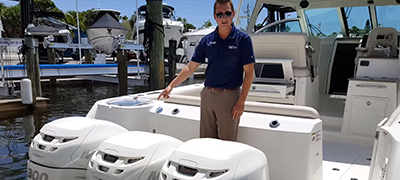 MarineMax employee on the aft of a docked boat pointing towards the engine