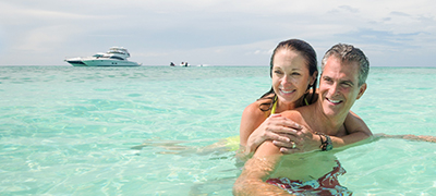 woman piggy backing on a man in clear turquoise waters with a yacht in the distance