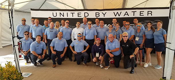 A group of MarineMax employees in light blue polo shirts lined up for a photo in front of a sign that says