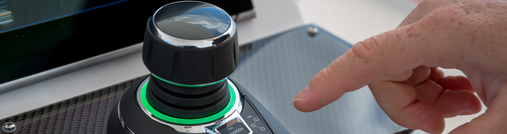 A hand pointing at a joystick on a boat