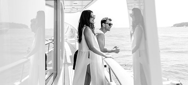 A man and woman standing on a yacht looking at the water