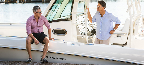 Two men talking on the side of the boat.