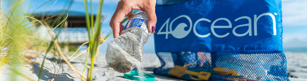 A plastic water bottle being picked up off of a beach with a 4Ocean logo in the background