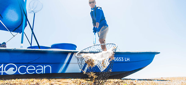 A man in a blue shirt standing on a blue boat, holding a net filled with trash on the surface of the beach